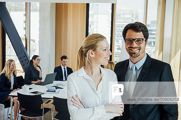Businessman and businesswoman in office with meeting in background