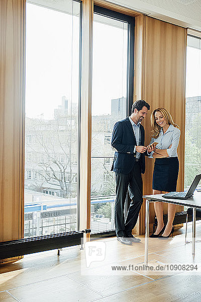 Businessman and businesswoman in office looking at cell phone