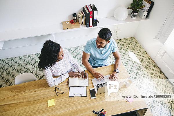 Junger Geschäftsmann und Frau arbeiten zusammen im Büro  mit Laptop