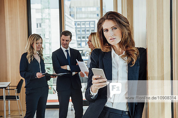 Businesswoman in office holding cell phone with businesspeople in background