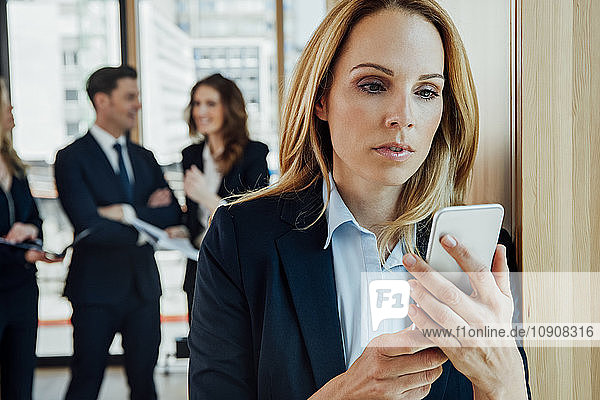 Businesswoman in office looking at cell phone with businesspeople in background