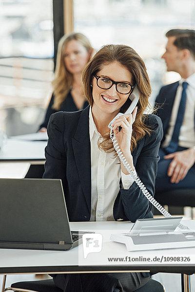 Lächelnde Geschäftsfrau am Schreibtisch am Telefon