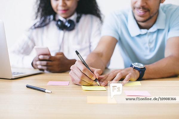 Junger Mann und Frau im Büro schreiben auf Haftnotizen auf dem Schreibtisch