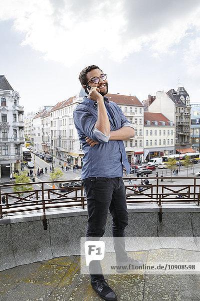 Junger Mann am Handy auf der Dachterrasse