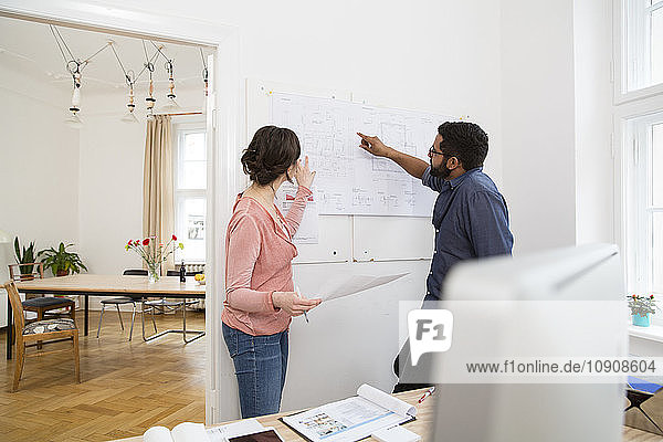 Man and woman discussing plan in office