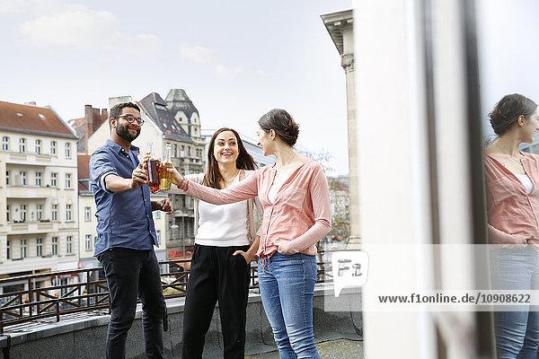 Mann und zwei Frauen klirren auf der Dachterrasse