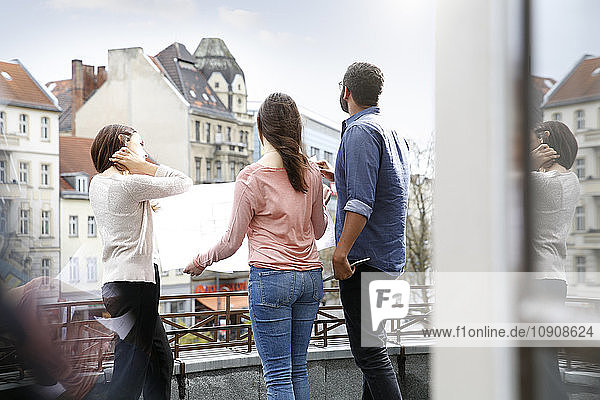 Man and two women standing on roof terrace looking at plan
