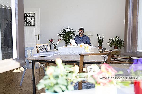 Young man working at table in office
