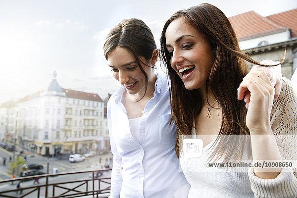 Zwei glückliche Frauen auf dem Balkon Zwei glückliche Frauen auf dem Balkon