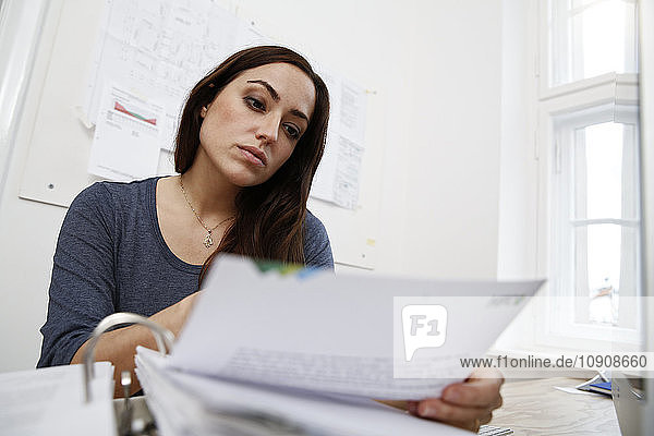 Woman working on files at office desk