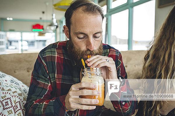 Bearded man drinking organic juice in cafe