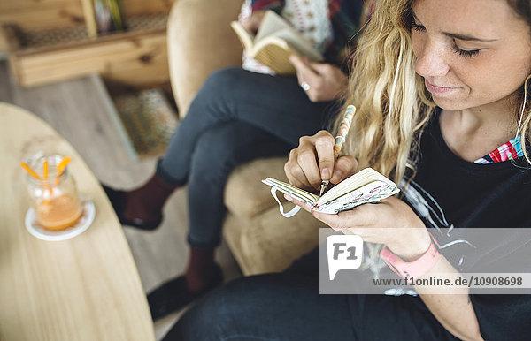 Paar im Café sitzend  Frau schreibt Tagebuch  Mann liest im Hintergrund