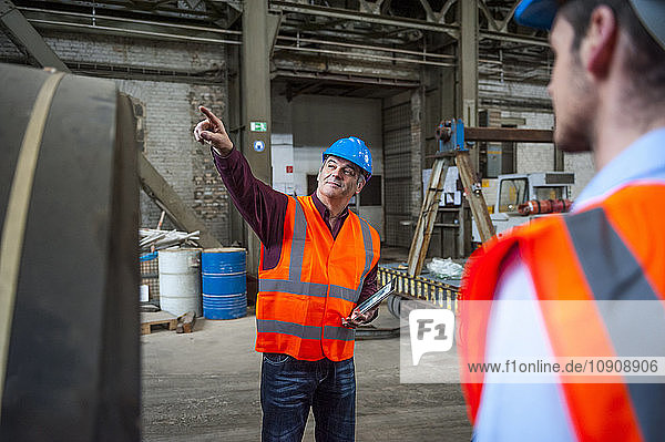 Man with safety vest in factory hall pointing his finger