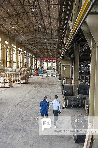 Two men walking through factory hall