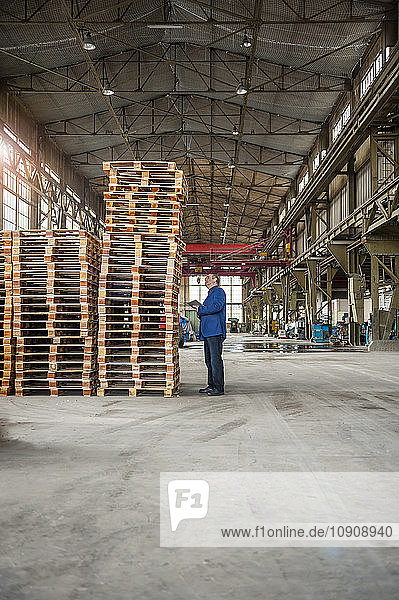Manager in factory hall looking at stack of pallets
