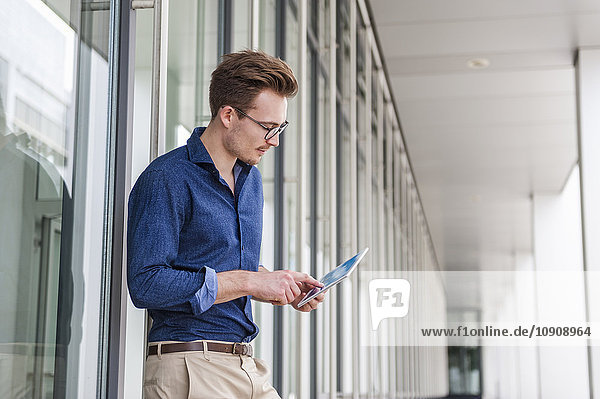 Young businessman standing in front of an office building using digital tablet