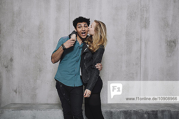 Couple in front of concrete wall  kissing