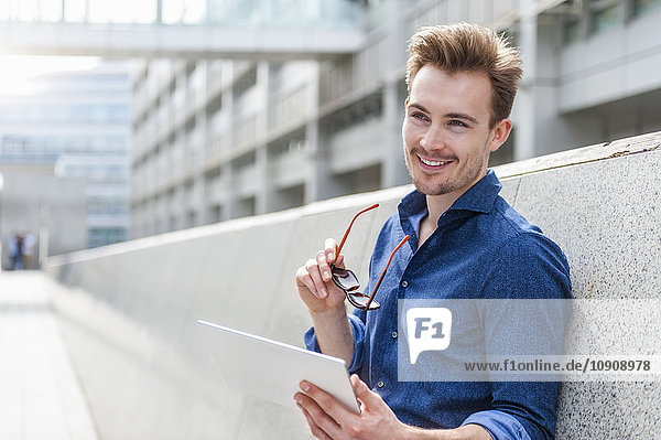 Portrait of young businessman with digital tablet leaning against wall