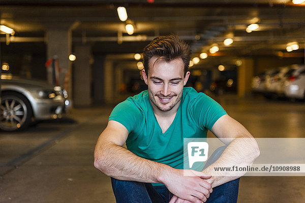 Portrait of smiling young man sitting in underground car park