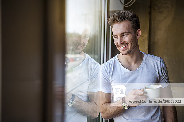 Portrait of houng man with cup of coffee looking through the window