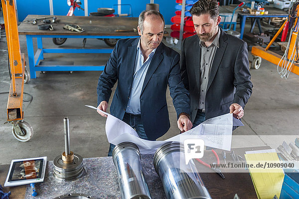 Two engineers with construction plan in front of hydraulic cylinder