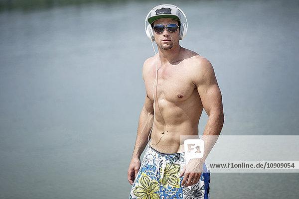 Porträt eines Mannes ohne Hemd  der Musik mit Kopfhörern vor einem See hört.