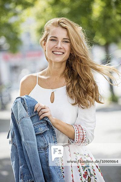 Porträt einer lächelnden jungen Frau im Freien