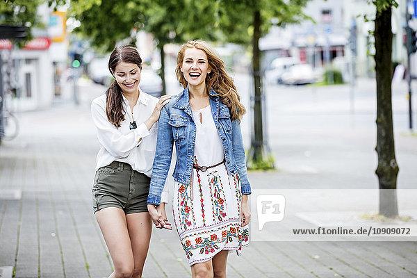 Zwei glückliche junge Frauen,  die in der Stadt spazieren gehen.