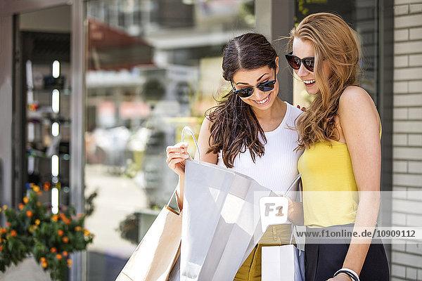 Zwei glückliche junge Frauen beim Blick in die Einkaufstasche