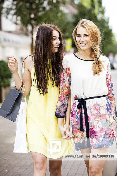 Zwei glückliche junge Frauen  die in der Stadt spazieren gehen.