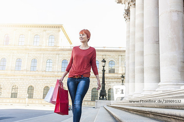 Smiling young woman walking with shopping bags
