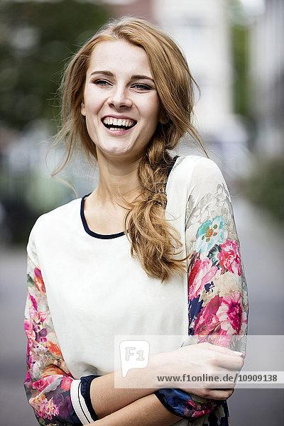 Porträt der lachenden jungen Frau im Freien