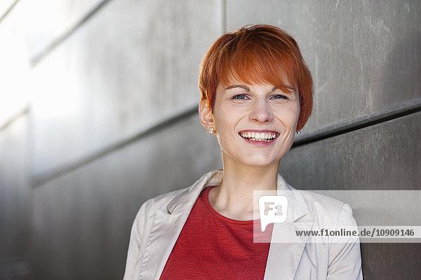 Porträt einer lächelnden rothaarigen jungen Frau