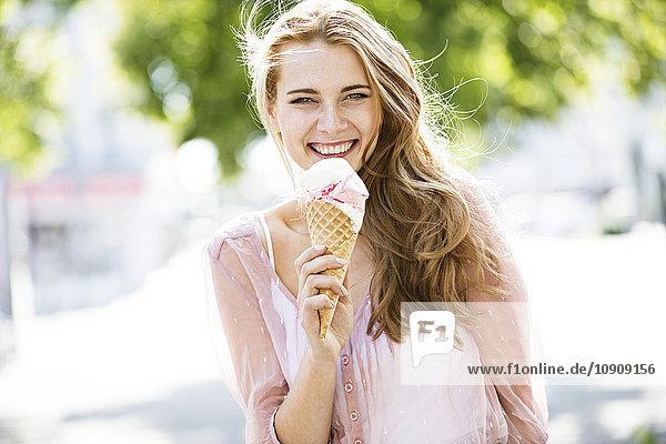 Porträt einer jungen blonden Frau beim Eis essen