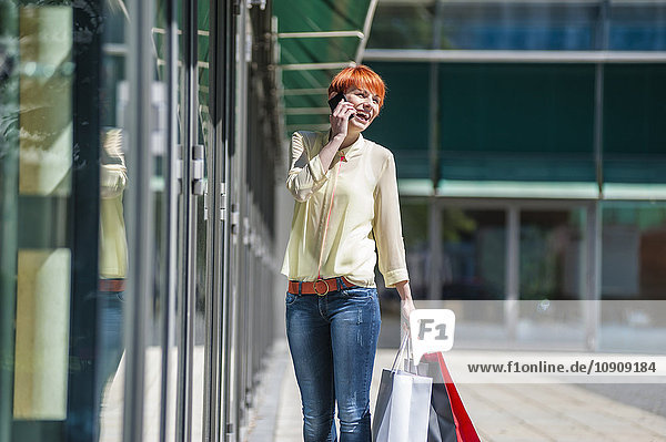 Glückliche junge Frau mit Einkaufstaschen am Handy