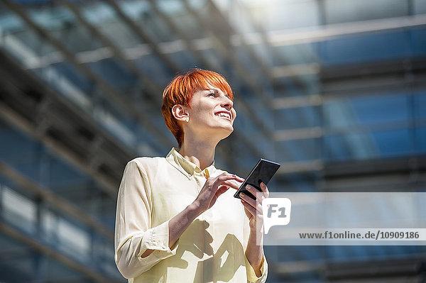 Lächelnde junge Frau im Freien mit Handy