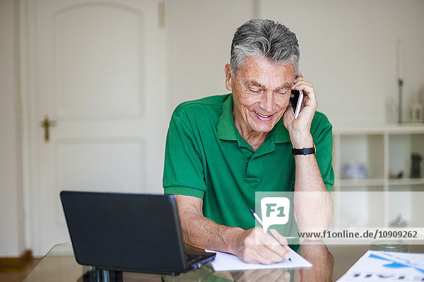 Älterer Mann sitzt am Schreibtisch und redet mit dem Handy.