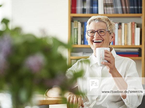 Porträt der lachenden Seniorin mit Tasse Kaffee zu Hause