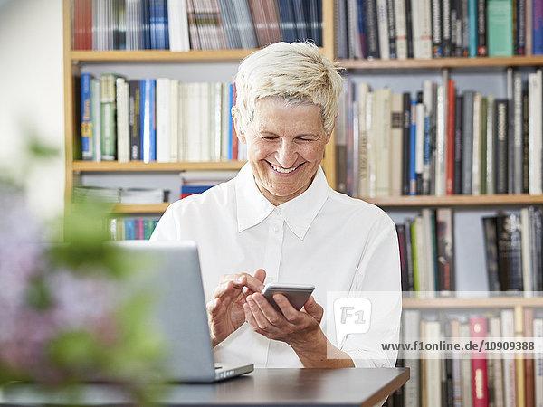 Porträt der lächelnden Seniorin mit digitalem Tablett und Smartphone zu Hause