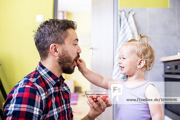Vater und Tochter essen Tomaten in der Küche