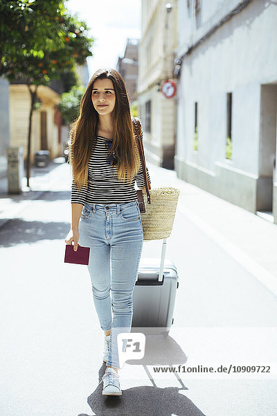 Young woman traveling with wheeled luggage