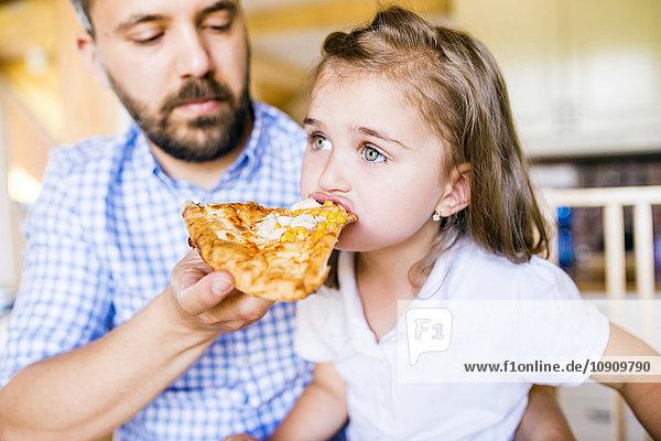 Vater füttert seine kleine Tochter mit Pizza.