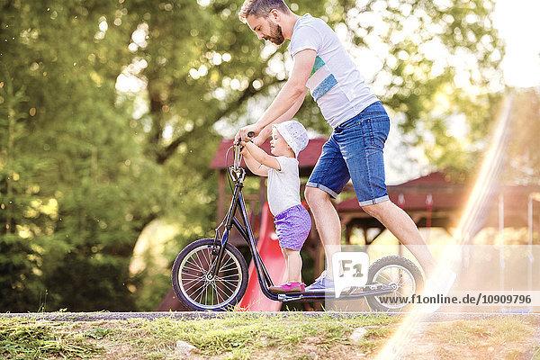 Vater und kleine Tochter zusammen auf einem Roller