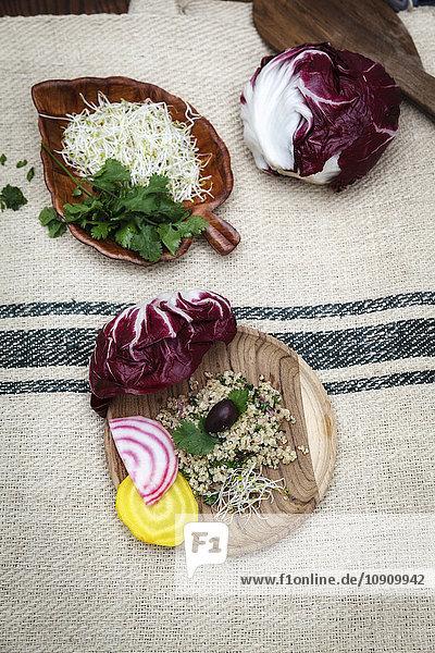 Quinoa-Salat  Radicchio  Rote Beete  gelb und rot auf Holzplatte