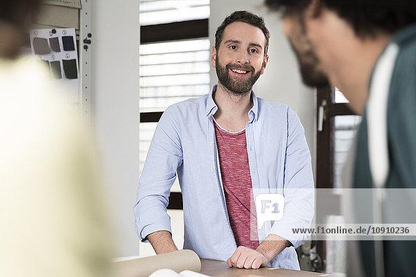 Lächelnder Kreativprofi im Büro mit Blick auf Kollegen