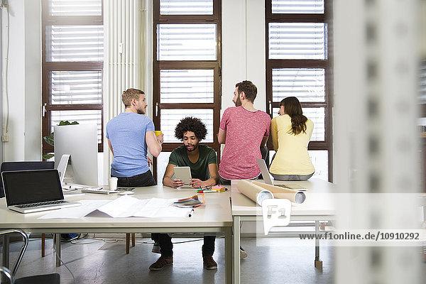 Team von Kreativprofis am Schreibtisch im Büro