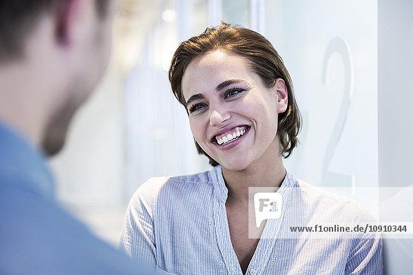 Porträt einer lächelnden Frau im Gespräch mit einem Mann
