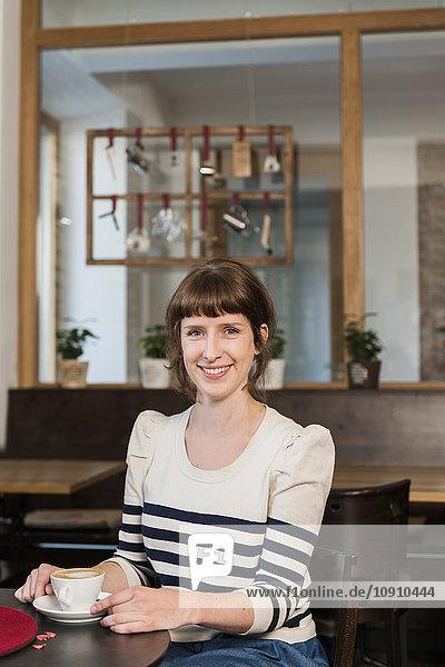 Porträt einer lächelnden Frau im Café mit Tasse Kaffee