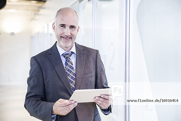 Reife Geschäftsleute mit digitalem Tablett