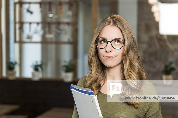 Portrait of sceptical blond woman with notebook in a coffee shop